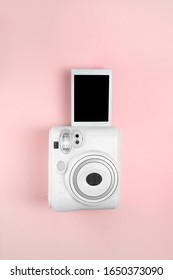 Modern instant camera, photo pink wooden background. vertical photo. retro camera. 1980s - Shutterstock ID 1650373090