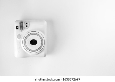 Modern instant camera, photo white wooden background. Top view, tender minimal flat lay style composition. fashion blogger, beauty technology