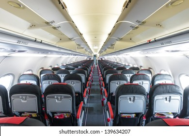 Modern interior of aircraft. Black and red seats inside airplane. Symmetric vanishing row of seats inside air transport. Economy class of flight. Equipment for travelling. Empty illuminated plane.