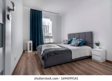 El moderno diseño de las habitaciones interiores con una cama gris y acogedora.
