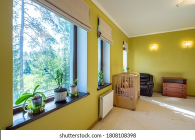 Modern interior of bedroom in private house. Wooden dresser and baby bed. Leather chaor. Green plants on sill.