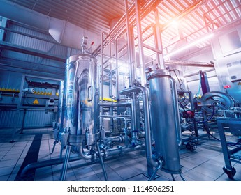 Modern interior of a brewery. Barrels and pipes. Factory interior. Industry background
