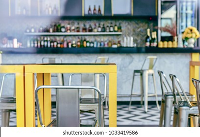 Modern Interior of Cozy Coffee Bar with Large Open Window Glass. Clean Table .Empty Slate Frames for Text Copy Space.Cafe Pub with Yellow Furniture During Day Background.