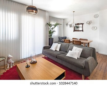 Modern interior decoration of a living room with a sofa, retro lamp, carpet, wooden floor, vintage wood chairs and table.
