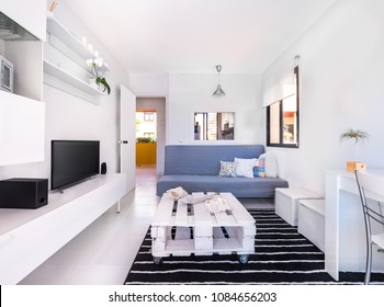 Modern interior decoration of a living room of a holiday destination flat with a sofa,television and white furnitures