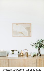 Modern interior design concept. Minimal Nordic Scandinavian style living room with photo frame on white wall, wooden table with gift box, floral bouquet with eucalyptus, candles, radio.
