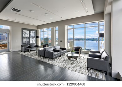 Modern interior design of living area with black leather armchairs and exit to luxurious terrace overlooking the Puget Sound. Northwest, USA