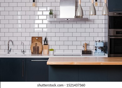 Modern interior design. Photo of kitchen with white tiles and dark furniture