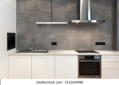 Modern interior design at white contemporary kitchen in loft style. Glossy cabinet with built in household appliance, electric stove, oven, sink on worktop and extractor hood on grey wall