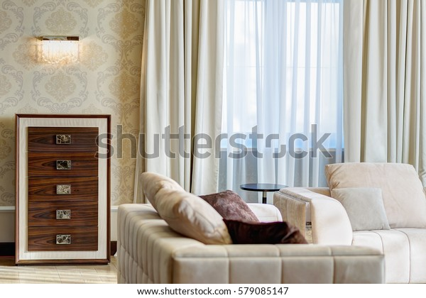 Modern interior of empty living room in brown, white, lithe brown colors, with pattern on wallpapers of walls. Two sofas with big pillows, wooden nightstand with drawers and lump on wall.