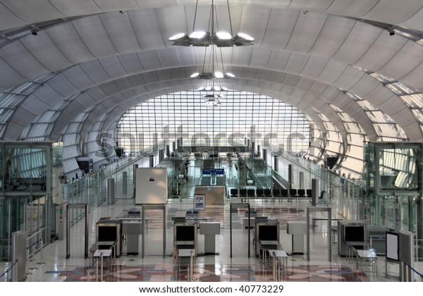 Modern interior of famous Bangkok Suvarnabhumi International Airport. Security control machines and departures area.