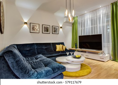 Modern interior in green, white and dark blue colors, living room with TV. Green curtain and cozy sofa with yellow pillows. Plate with fruits on glasses table near.