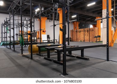 Modern interior of the gym for fitness training with horizontal bar and barbells