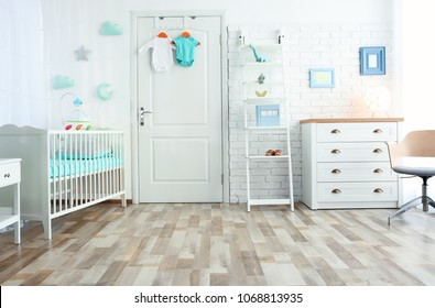 Modern interior of light cozy baby room with crib