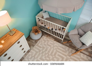 Modern interior of light cozy baby room with crib, view from above