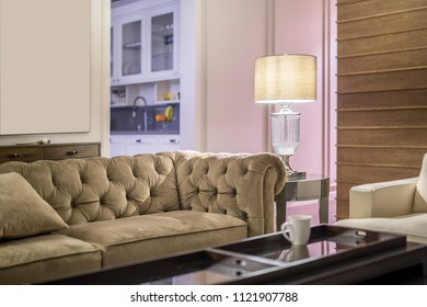 Modern interior with light walls. There are multicolored sofas with pillows, different tables, fancy luminous lamp, wooden stand with lockers, kitchen zone with a sink and shelves. Horizontal.