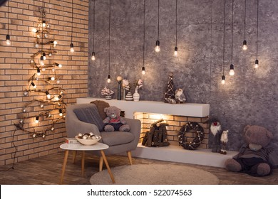 Modern interior of living room. Creative Christmas tree, contemporary fireplace and large gray armchair in loft interior design apartment.