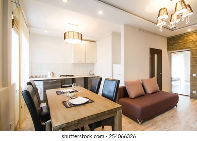 Modern interior of a living room studio. Large spacious kitchen in moderate tone. A large wooden table in the interior