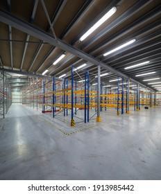 Modern interior of new empty warehouse. Racks pallets shelves. Metal construction. Storage equipment.