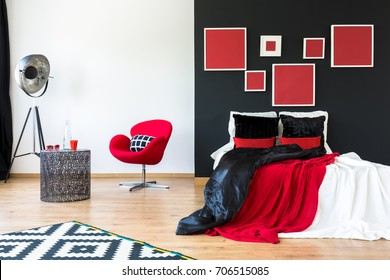 Modern interior with red paintings on black wall above king-size bed with contrast colored pillows