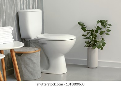 Modern interior of restroom with ceramic toilet bowl
