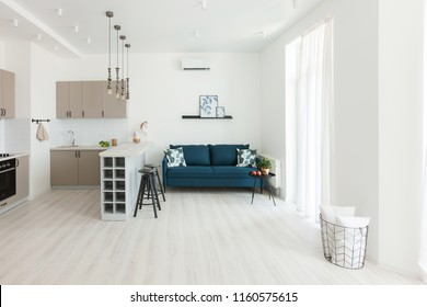Modern interior of the Room in the House or Apartment. Blue Sofa with pillow and plaid in white simple living room.