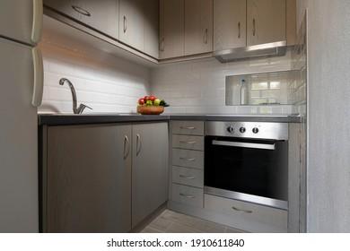 Modern interior of small corner kitchen with white subway brick tile splashback. Fruit plate on light wooden cabinets background