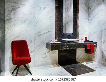 The modern interior of the washroom with black and white marble tiles, decorated with red accessories