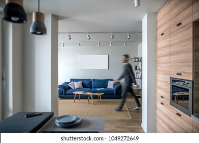Modern interior with white walls and parquet with a carpet on the floor. There is a kitchen zone with wooden lockers and oven, room with a walking man, blue sofa with pillows, wooden tables, shelves.