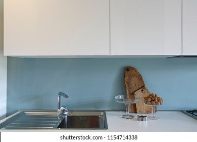 modern interiors shot of a kitchen in the foreground the steel kitchen sink with tap and glass containers with walnuts on the worktop
