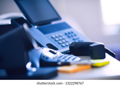 Modern ip phones, sip terminals, conference phones and cameras for video meetings on the office table. Close up.