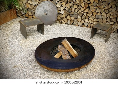 Modern Iron Decorative Fireplace  On The Marble Gravel Floor On The Backyard, Wall Of Firewood In The Background. Garden Design Element