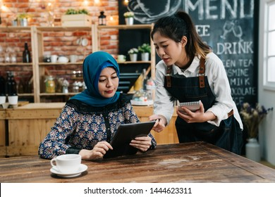 Modern islam businessman reading menu on tablet in cafe bar while waitress recommending guest something special. young girl waitress taking order point to touch pad in coffee shop giving advice.