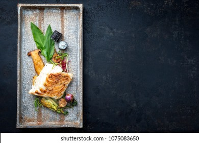Modern Japanese fried cod fish filet with bok choi and sushi rolls as top view on a plate with copy space right