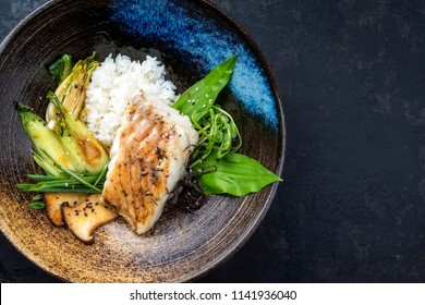 Modern Japanese fried cod fish filet with bok choi and rice as top view in a bowl with copy space right