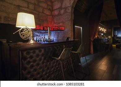 Modern jazz bar interior design, leather bar counter, lamp like music instrument design. Stone wall on background, brutal atmosphere