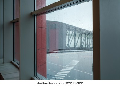 Modern jetway located on airfield behind wet window of aerodrome on rainy day