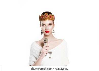 Modern journalist. Beauty queen speaking singing karaoke having speech propaganda on microphone isolated white background wall. Girl with golden ruby crown jewelry red lips perfect makeup, mic