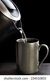 Modern kettle pouring water into a cup on a black background
