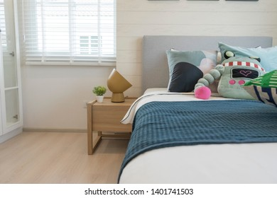 modern kid's bedroom with green, blue and robot doll pillows on it.