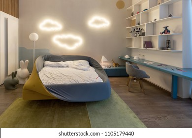 Modern kid's room with luminous fancy cloud lamps on a white wall. There is colorful bed with white linens, blue tabletop with gray chair, white shelves with toys and books, stand with lamp and toys.