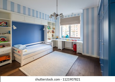 Modern kid's room with striped blue-white walls and a parquet with a carpet on the floor. There is a white bed with pillows, lockers and shelves with toys and books, table, blue wardrobe, window, bin.