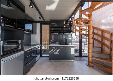 Modern kitcen interior in cottage with wooden spiral staicases