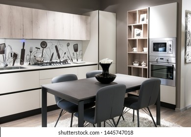 Modern kitchen with artistic splash back above a white counter, built in cabinets and appliances and a central table and chairs in a stylish beige brown decor