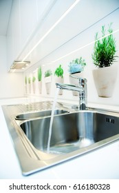 modern kitchen with bassin and running water from tap.