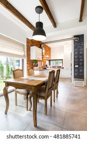 Modern kitchen with big table and brick wall
