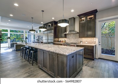 Modern kitchen with brown kitchen cabinets, oversized kitchen island with bar stools, granite countertops, huge refrigerator and beige backsplash. Northwest, USA