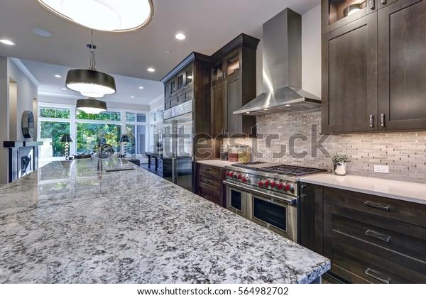 Modern kitchen with brown kitchen cabinets, oversized kitchen island, granite countertops, stainless steel hood over six burner Range and beige backsplash. Northwest, USA