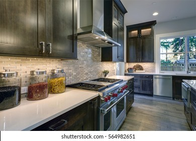 Modern kitchen with brown kitchen cabinets paired with white countertops, stainless steel hood over six burner Range and beige backsplash. Northwest, USA