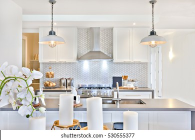 Modern Kitchen With Candles And White Flowers Beside Counter Top Including  Tap And Sink. There